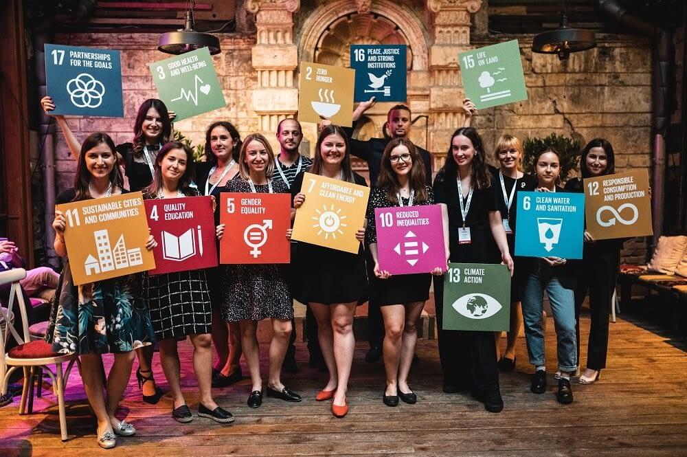A képen a V4SDG – Visegrád a Fenntarthatóságért fiatal csapata látható, a fenntartható fejlődés témájához kapcsolódó molinókkal.