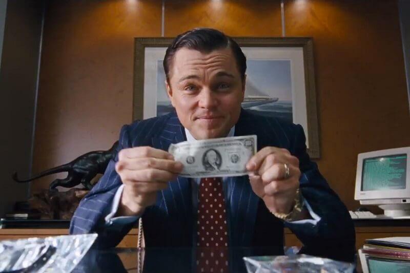 A képen egy jelenet látható a Wall Street farkasából. DiCaprio egy 100 dollárost tart a kezében
